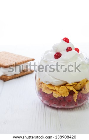 glass with cream, corn flakes and cranberries on a white background