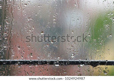 Glass with droplets and streams of rain and blurred bright pink and green silhouettes behind the glass.