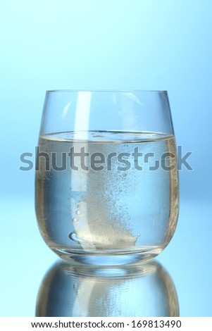 Glass with efervescent tablet in water with bubbles on blue background