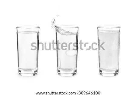 Glass with effervescent tablet in water with bubbles on white background - stock photo