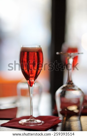 Glass with French alcohol drink Kir Royal on the table at the restaurant  - stock photo