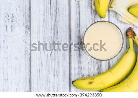 Glass with fresh made Banana juice (selective focus) on an old wooden table - stock photo