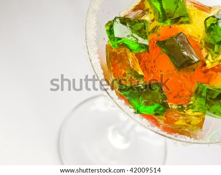 Glass with fruit jelly cubes. Shallow dof. - stock photo