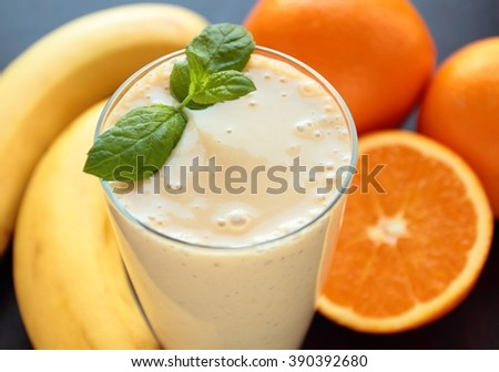 Glass with healthy smoothie with banana and oranges decorated with fresh mint leafs