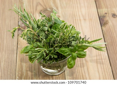 Glass with Herbs on wooden background - stock photo