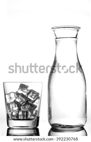 Glass with ice and a bottle of water on a white background.