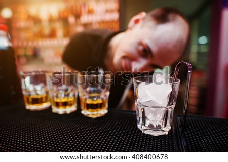 Glass with ice and tongs with three whiskey glasses background funny barman