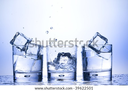 Glass with ice and water splashing