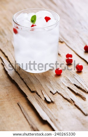 Glass with ice cubes on wooden table - stock photo