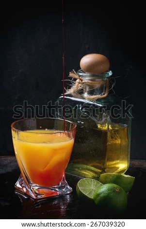 Glass with ice cubes, orange juce and pouring grenadine, and bottle of tequila, served with sliced limes over black background. Making tequila sunrise cocktail. - stock photo