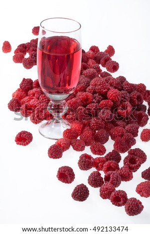 Glass with juice and raspberries on an isolated studio background