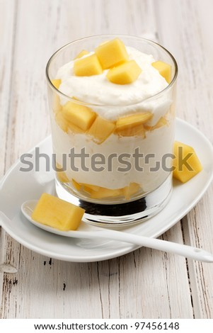 Glass with layered mango and creme. - stock photo