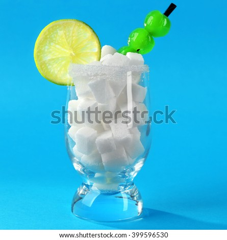 Glass with lump sugar, cocktail cherries and lime slice on blue background - stock photo