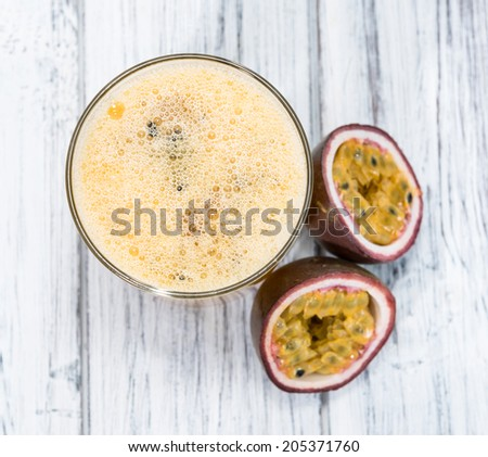 Glass with Maracuja Juice and fresh fruits on wooden background - stock photo