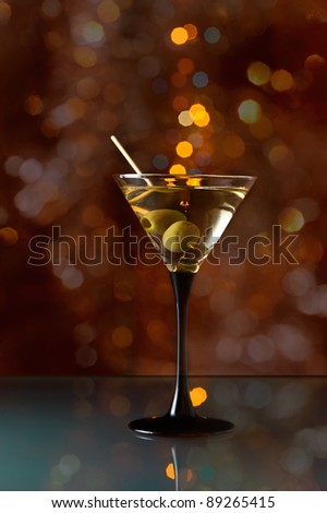 glass with martini and green olives on a dark background. - stock photo