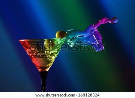 glass with martini and green olives on dark background - stock photo