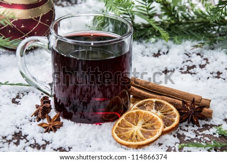 Glass with mulled wine on a snow covered background - stock photo