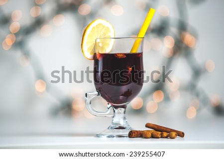 Glass with mulled wine on blurred background
