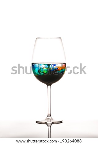 Glass with multicolored water on white background, concept of polution - stock photo