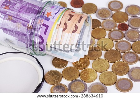 Glass with paper money and coins - stock photo