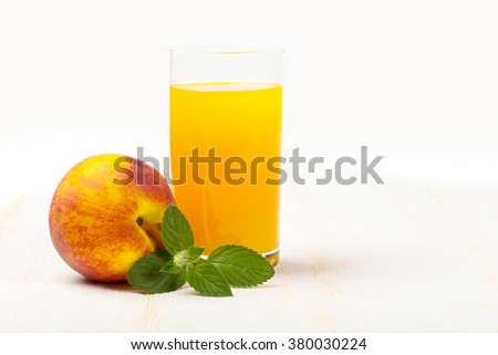 Glass with peach juice and ripe peach and green mint on white wooden surface - stock photo