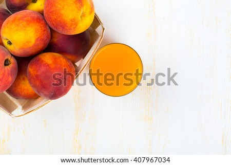 Glass with peach juice and ripe peaches in basket on white wooden surface. Top view. - stock photo