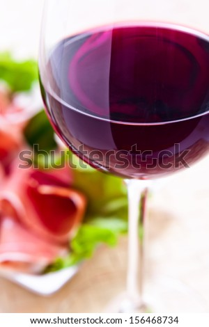 glass with red wine and ham with salad  - stock photo