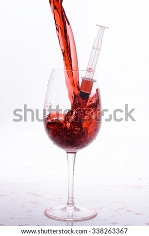 glass with red wine and syringes