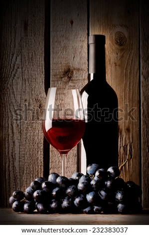 Glass with red wine bottle and grapes on a wooden background