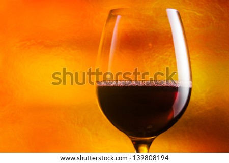 glass with red wine on a orange background - stock photo