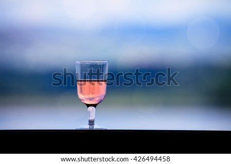 glass with rose wine over the bokeh nature background  - stock photo