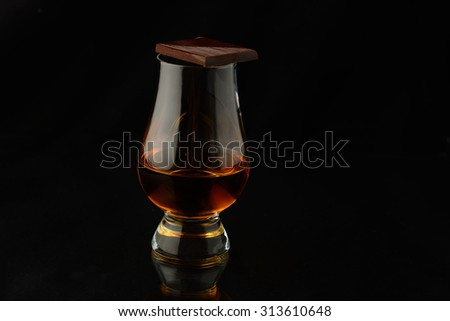 Glass with single malt whisky isloated over black background - stock photo