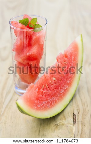 Glass with some pieces of watermelon and a piece of watermelon