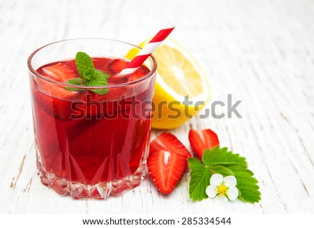 Glass with strawberry drink on a wooden background - stock photo