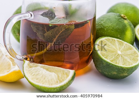 Glass with tea and mint and limes and lemon on the side