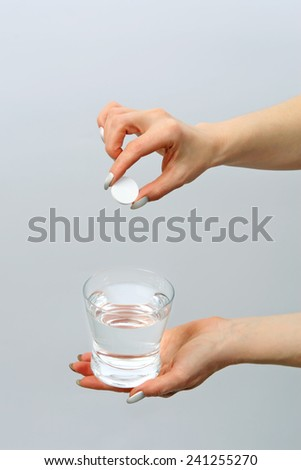 Glass with water and effervescent tablet in a female hands - stock photo