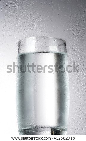 Glass with water and water drops - stock photo