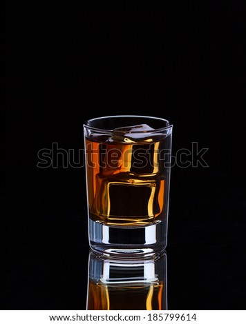 Glass with whiskey and ice cubes on dark background, selective focus  - stock photo