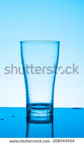 glass with wine on blue background - stock photo