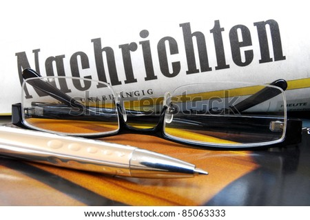 """Glasses and ball pen on top of a multicolored cover with lettering """"News"""" in German language - stock photo"""