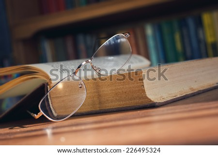 glasses and book on background bookcase - stock photo