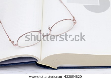 Glasses and book on the white wooden table - stock photo