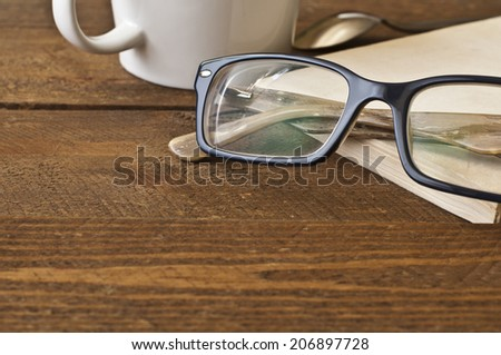 Glasses and book on wood. Warm natural light. - stock photo
