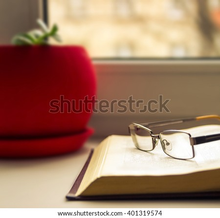 Glasses and books - classy attribute of intelligence. Sunlight, sunshine. book and glasses. flower pot - stock photo