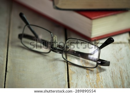 Glasses and books on an old wooden surface