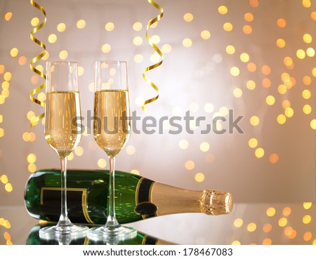 Glasses and bottle of champagne on shiny background