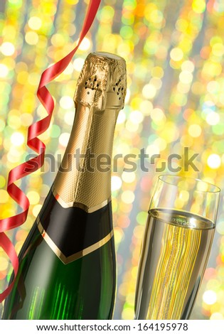 Glasses and bottle of champagne, serpentine  isolated on a holiday bokeh background. Celebration. New Year Card Design with Champagne. Christmas Scene.  - stock photo