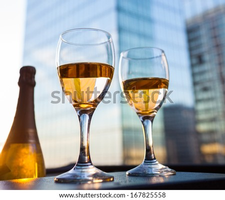 Glasses and bottle of white wine  with the modern city view - stock photo