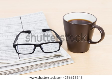 Glasses and business newspapers with coffee