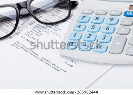 Glasses and calculator over utility bill - stock photo